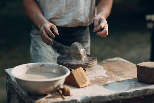 Potter robi gliniany dzbanek na kole garncarskim