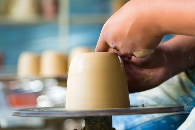 Potter tworzy glinianą miskę na obracającym się kole