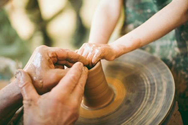Potter uczy rzeźbić glinianą doniczkę