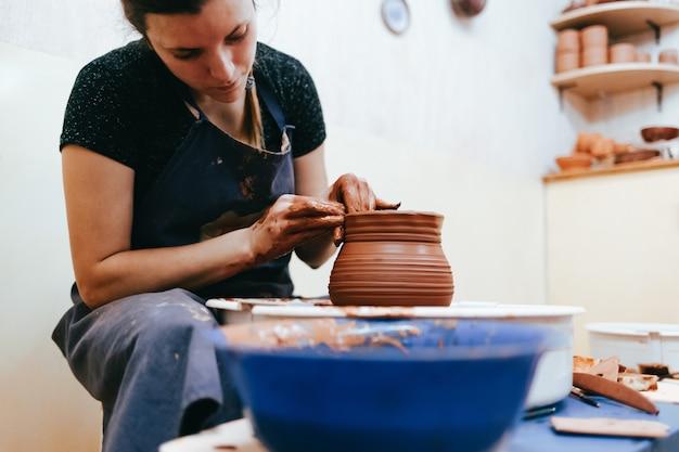 Potter za kołem garncarza tworzy glinę, aby tworzyć naczynia ceramiczne