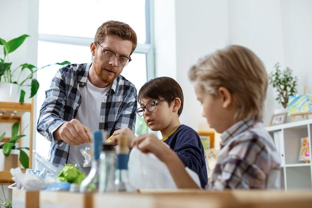 Pouczająca lekcja ekologii. brodaty nauczyciel w kraciastej koszuli pomaga swoim uczniom rozdzielać śmieci do różnych pudeł