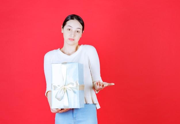 Poufna kobieta trzyma pudełko i otworzyła dłoń