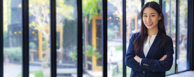 Poufne biznes asian młoda kobieta krzyż uzbrojony i wygląd aparatu w biurze