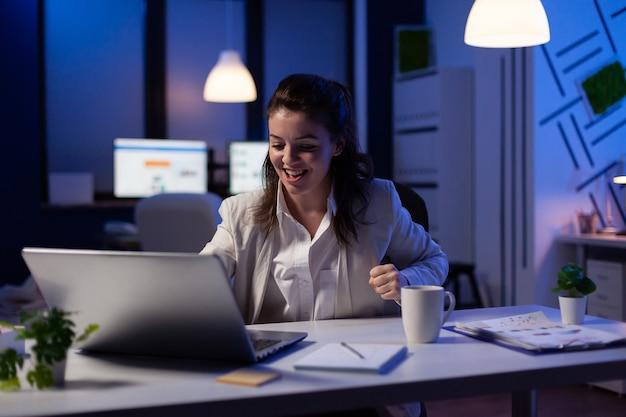Pov businesswoman prowadzącej wideokonferencję z zespołem siedzącym w biurze firmy o północy
