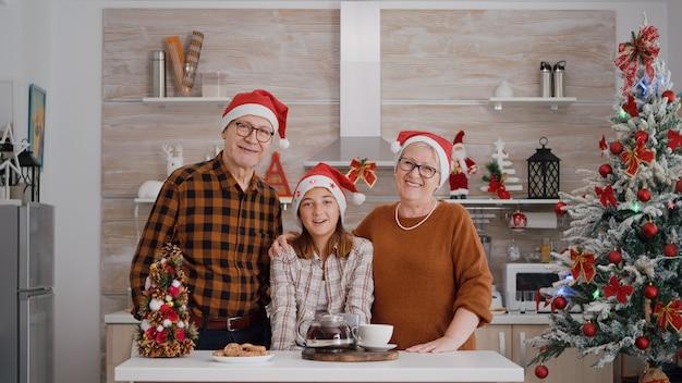 Pov dziadków z wnuczką rozmawiających o feriach zimowych ze zdalnymi przyjaciółmi