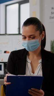 Pov kobiety biznesu z maseczką medyczną pracującą nad projektem komunikacyjnym z zespołem podczas wideokonferencji online