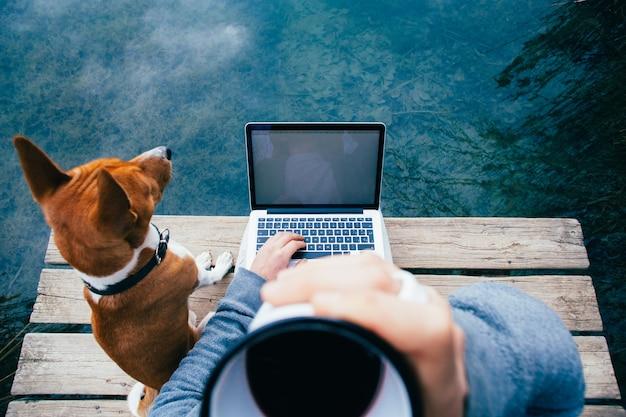 Pov mężczyzny pije kawę i pracuje na laptopie nad jeziorem