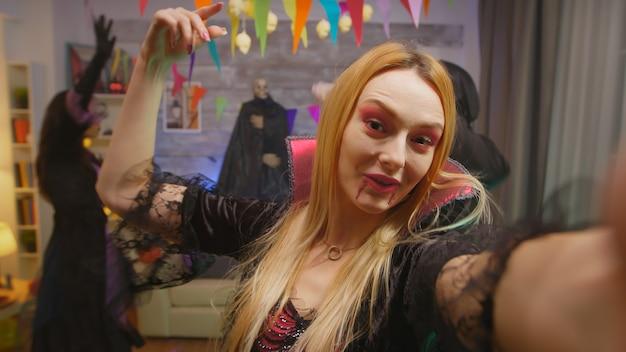 Pov młodej kobiety ubranej jak czarodziejka zapraszająca przyjaciół na przyjęcie z okazji halloween, podczas gdy inni ludzie tańczą w tle w udekorowanym domu