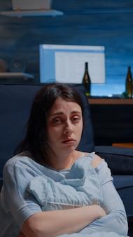 Pov nieszczęśliwej przygnębionej kobiety płaczącej trzymającej poduszkę siedzącą na podłodze