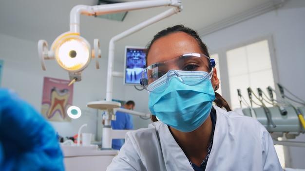 Pov pacjenta w gabinecie stomatologicznym, siedzącego na fotelu chirurgicznym, sprawdzającego zaatakowaną masę. zespół stomatologa pracujący w gabinecie ortodontycznym, oświetlenie lampy i osoba badająca, zbliżenie twarzy w masce medycznej.