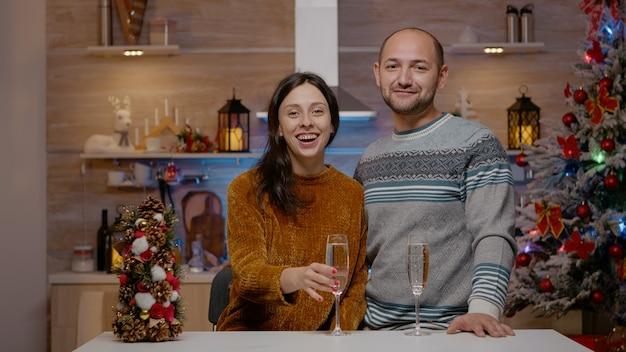 Pov para korzystająca z wideorozmowy i podnosząca kieliszki szampana