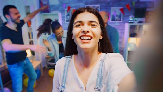 Pov pięknej młodej kobiety podczas wideorozmowy na imprezie z przyjaciółmi.
