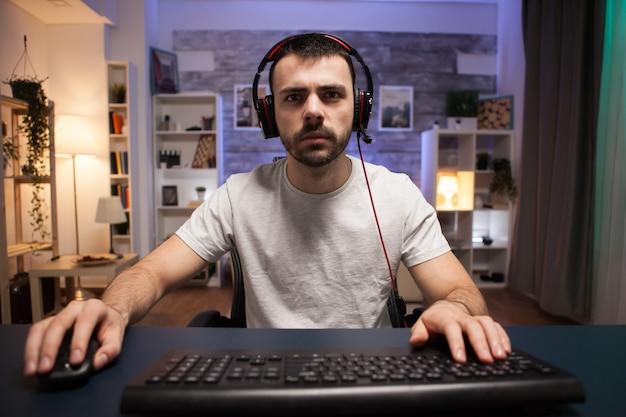 Pov rywalizującego młodego mężczyzny grającego w strzelanki online na swoim komputerze w pokoju z neonowym światłem. człowiek ze słuchawkami.