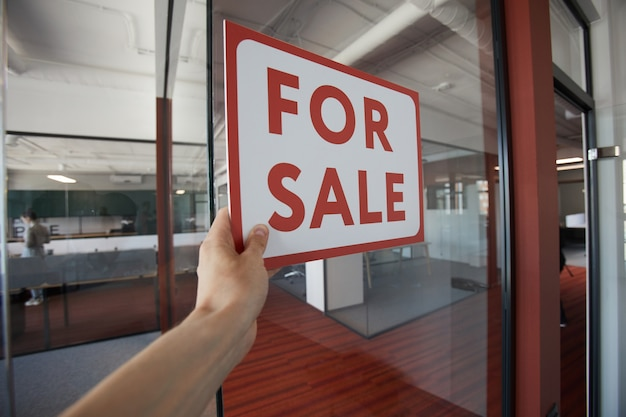 Pov strzał nierozpoznawalnego mężczyzny wiszący czerwony znak sprzedaży na szklanych drzwiach biurowca, miejsce na kopię