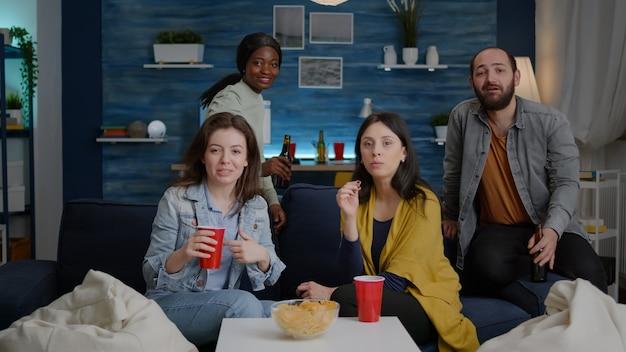 Pov wieloetnicznych przyjaciół zbierających się późno w nocy na kanapie podczas imprezy w mieszkaniu, rozmawiających na spotkaniu online z przyjacielem z afrykańskiego college'u. osoby wielorasowe spotykające się ze wspólną zabawą