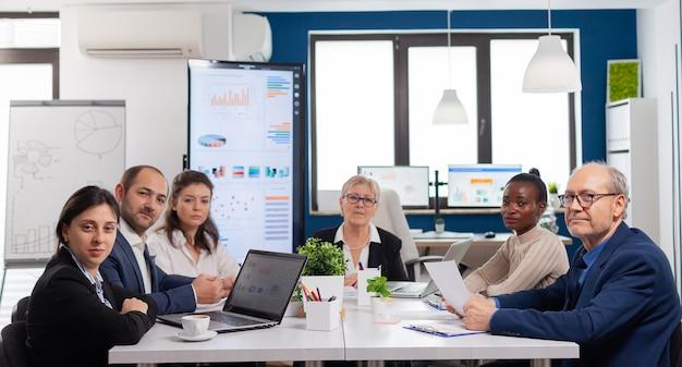 Pov zróżnicowanego zespołu siedzącego w sali konferencyjnej podczas wirtualnego spotkania, dyskutującego online z partnerami biznesowymi