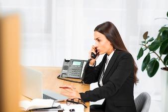 Poważny młody bizneswomanu obsiadanie przy biurkiem opowiada na telefonie