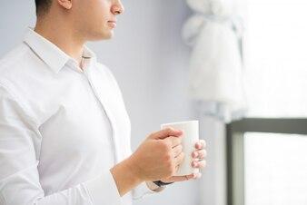 Poważny zadumany biznesmen pije kawę w biurze