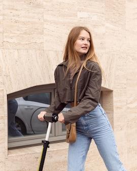 Powabna kobieta jedzie na zewnątrz skuterem elektrycznym