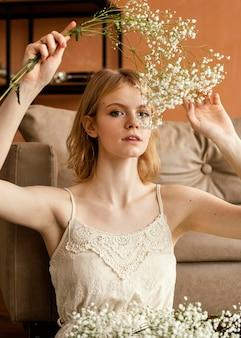 Powabna kobieta pozuje obok sofy trzymając delikatne wiosenne kwiaty
