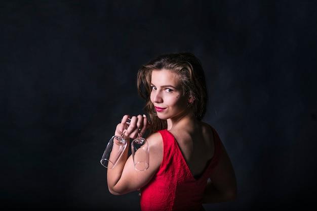 Powabna kobieta pozuje podczas gdy trzymający szkło