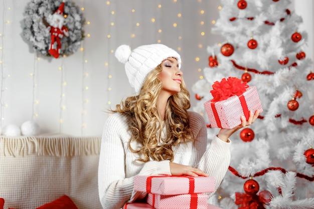 Powabna kobieta pozuje z bożenarodzeniowymi prezentami
