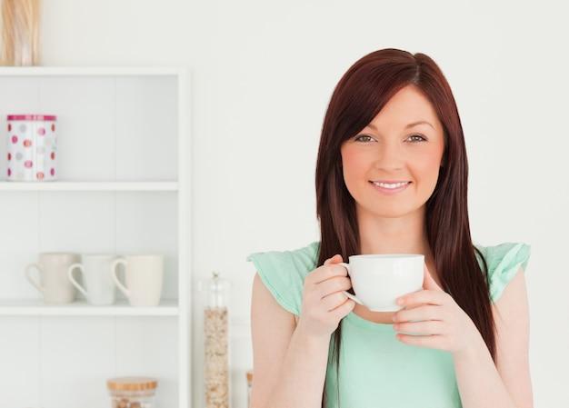 Powabna miedzianowłosa kobieta ma jej śniadanie w kuchni