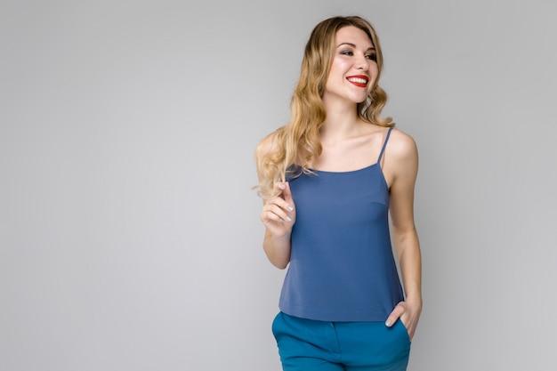 Powabna młoda blondynki dziewczyna ono uśmiecha się na szarym tle w błękitów ubraniach