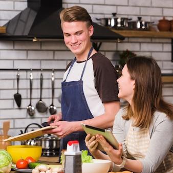 Powabna para używa pastylkę gotować w kuchni