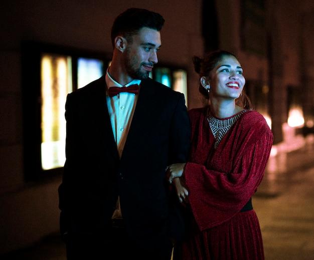 Powabny atrakcyjny uśmiechnięty kobiety odprowadzenie z młodym człowiekiem na ulicie