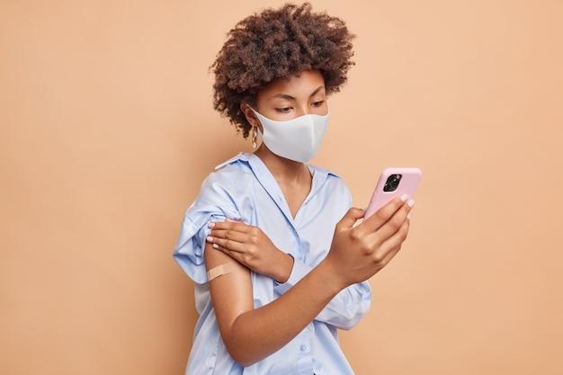Poważna afroamerykanka z kręconymi włosami pobiera specjalną aplikację na smartfona, aby uzyskać świadectwo szczepienia online, nosi jednorazową maskę na twarz i pokazuje oklejone ramię po zastrzyku szczepionki