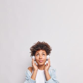 Poważna afroamerykańska studentka słucha wykładu lub webinaru online przez słuchawki skupione na górze, cieszy się dobrym dźwiękiem, nosi dżinsową koszulę na tle białej ściany, miejsce na reklamę