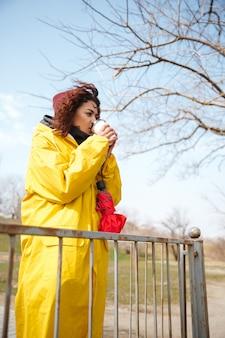 Poważna afrykańska kędzierzawa młoda dama patrzeje na boku i pije kawę.