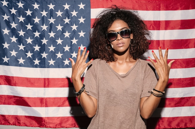 Poważna afrykańska młoda dama stoi nad usa flaga