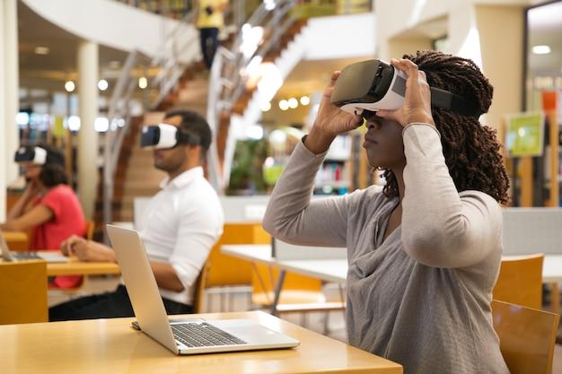 Poważna amerykanin afrykańskiego pochodzenia kobieta jest ubranym okulary wirtualnej rzeczywistości