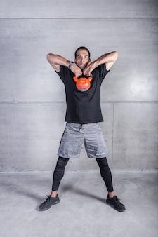 Poważna atleta robi ćwiczeniu z kettlebell
