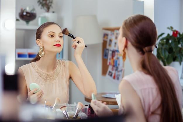 Poważna atrakcyjna kobieta nakłada puder na twarz, chcąc wyglądać naturalnie