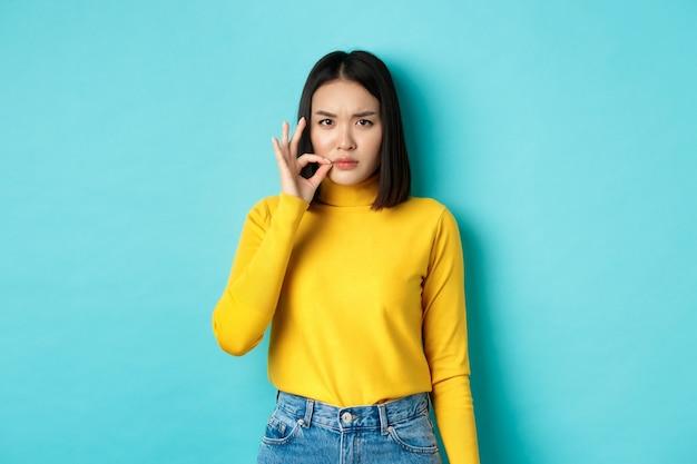 Poważna azjatka pokazująca gest suwaka w buzi, obiecuje się zamknąć i marszcząc brwi, opowiadając wielką tajemnicę, stojąc w żółtym swetrze na niebieskim tle.