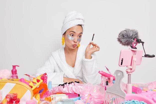Poważna azjatycka blogerka zajmująca się urodą nagrywa wideo do swojego vloga o urodzie, trzyma pędzelek kosmetyczny, nakłada opaskę na oczy, opowiada o zabiegach pielęgnacyjnych, robi makijaż w domu przed kamerą smartfona
