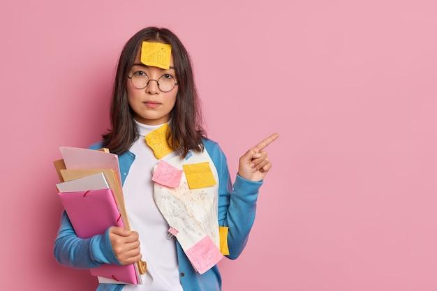 Poważna azjatycka pracownica biurowa trzyma pliki przyklejone samoprzylepnymi karteczkami na bok i pokazuje, że coś w pustym miejscu nosi okrągłe okulary.
