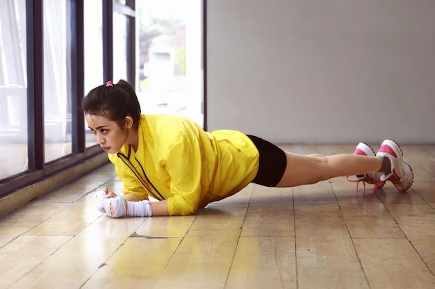 Poważna azjatykcia kobieta robi deska treningowi