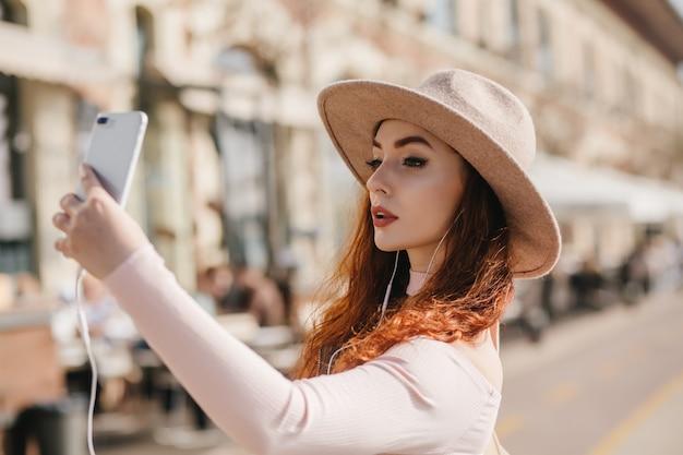 Poważna biała kobieta z ciemnym makijażem robi sobie zdjęcie