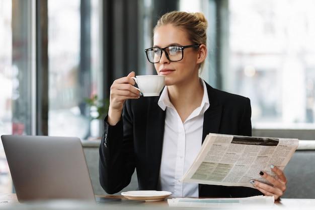 Poważna biznesowa kobieta czyta gazetę.
