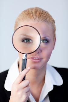 Poważna biznesowa kobieta patrzeje przez powiększać - szkło