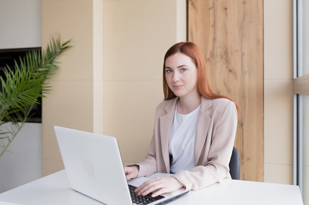 Poważna biznesowa kobieta pracująca na laptopie siedząca przy biurku
