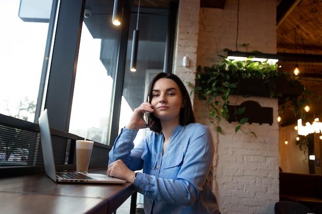 Poważna biznesowa kobieta rozmawia przez telefon i patrzeje kamerę. widok z boku. przytulna atmosfera kawiarni. freelancer korzystający z nowoczesnego laptopa do pracy. młoda współczesna kobieta pracuje na freelance.