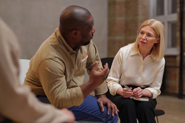 Poważna blond doradczyni w eleganckim stylu casual, patrząca na siedzącego obok niej afrykańskiego pacjenta i opisującego swój problem