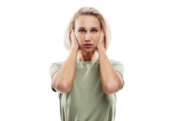Poważna blond kobieta zakrywająca uszy rękami. fobia społeczna i problemy psychologiczne. na białym tle na białej ścianie.