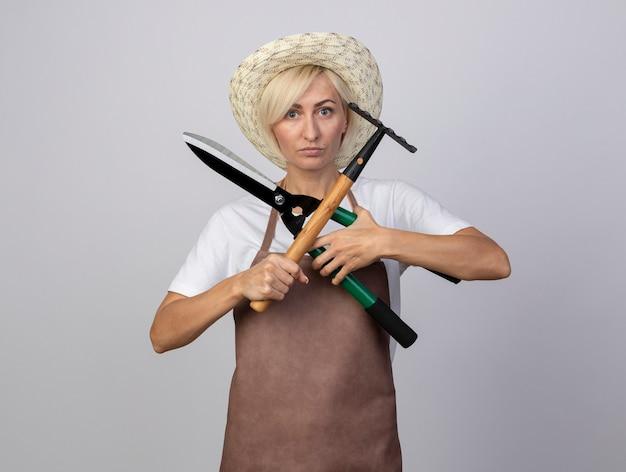 Poważna blond ogrodniczka w średnim wieku w mundurze, w kapeluszu, trzymająca nożyce do żywopłotu i grabie, nie robiąc z nimi żadnego gestu