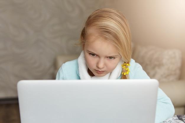 Poważna blondynka mała dziewczynka siedzi przed otwartym laptopem